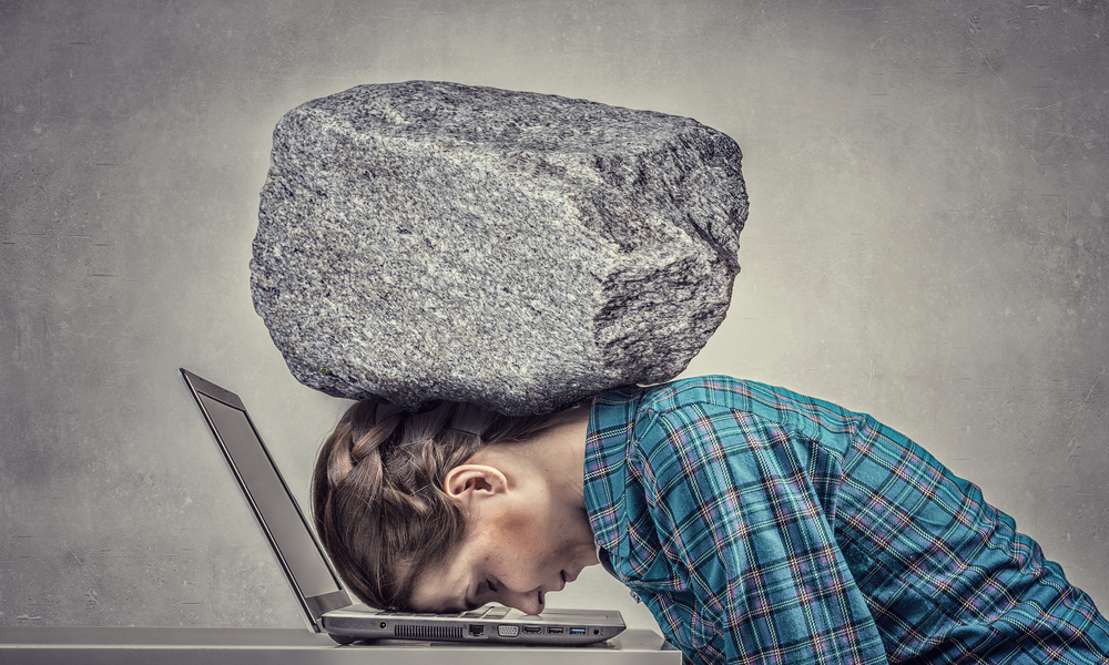 Woman with head on laptop and a huge rock on back of her head illustrates article on business coaching and life coaching.